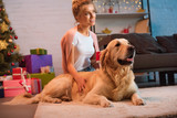 beautiful smiling young blonde woman sitting on floor with golden retriever dog at christmas time
