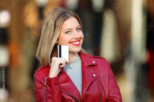 Leinwandbild Motiv Happy shopper showing blank credit card in a mall