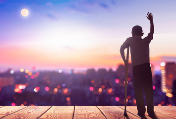 International Day of Persons with Disabilities concept? Silhouette a disabled man standing at mountain city background