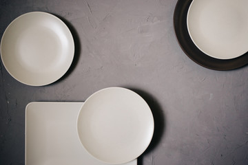 Top view of set ceramic dishes brown and milky white colored, on gray background