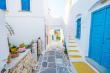 Colorful stairs in narrow street with white houses and blue colored windows. Old rustic Greek house exterior - 234251300