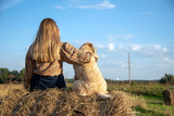 A girl with long hair sits next to a shaggy dog on a haystack with her back to the camera