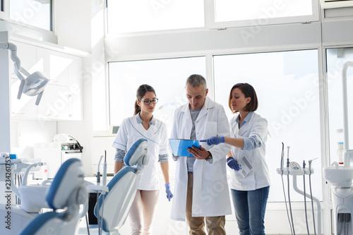 fototapeta na ścianę Medical dentist team in dental office examining list of patients.