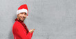 Man with red clothes celebrating the Christmas holidays pointing back and presenting a product on textured background