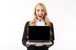 Leinwandbild Motiv Photo of beautiful businesswoman wearing office suit smiling while holding laptop with black screen, isolated over white background in studio