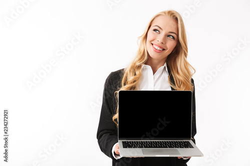 Leinwandbild Motiv Photo of caucasian businesswoman wearing office suit smiling while holding laptop with black screen, isolated over white background in studio