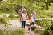 Family Hiking Along Path By River In UK Lake District