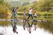 Leinwanddruck Bild - Family Crossing River Whilst Hiking In UK Lake District