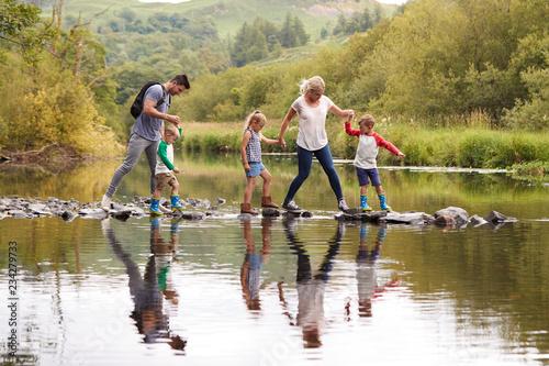 Leinwanddruck Bild Family Crossing River Whilst Hiking In UK Lake District