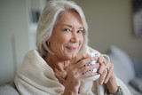 Cosy looking senior woman at home with hot drink