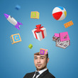 A view of a handsome young man with head cracked open and a bunch of toys popping out of it isolated on blue background.