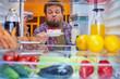 Leinwanddruck Bild - Man standing and taking gateau from fridge.  Picture taken from the inside of fridge.