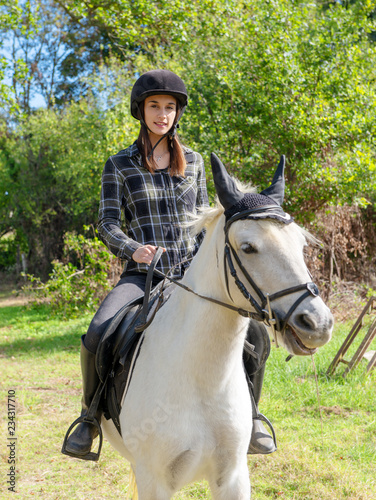 Young woman with black helmet riding white horse