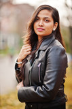 Close up portrait of pretty indian girl in black saree dress and leather jacket posed outdoor at autumn street. - 234320942