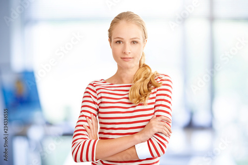 Leinwanddruck Bild Young beauty female portrait. Attractive young blond woman wearing striped shirt while looking at camera and smiling.