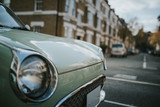 Vintage car headlamp with a classic english street in the background.