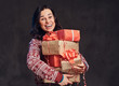 Quadro Portrait of a happy brunette girl wearing a warm sweater holding a gifts boxes, isolated on a dark textured background.