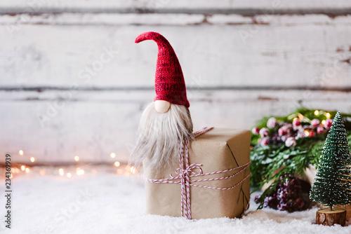 Leinwandbild Motiv Bald ist Weihnachten! Kleiner Wichtel sitz auf Geschenk  vor weihnachtlich, winterlicher Dekoration