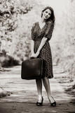 Style cuacasian adult girl in dress with travel suitcase staying on rural road. Image in black and white color style - 234371132