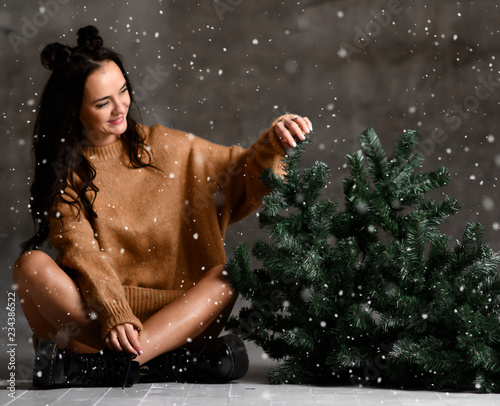 Leinwandbild Motiv Beautiful hipster woman sitting with Christmas fir tree in sexy knitted sweater blouse under snow