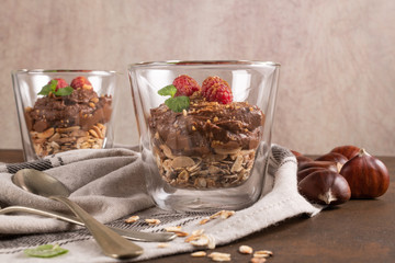 Glass cups of chocolate and chestnuts mousse with roasted almonds and oats decorated with raspberry and mint leaves