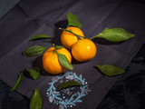 Three mandarins with green leaflets on a decorative cotton decorative napkin.