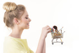 Woman holding shopping cart with make up brushes - 234416577