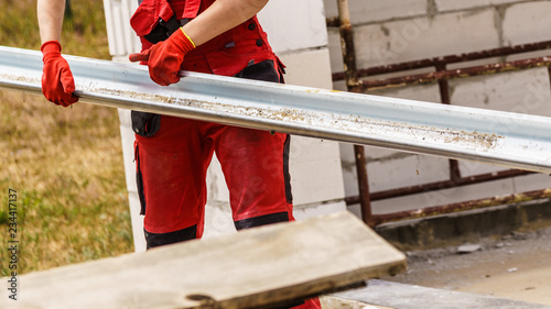 Person carrying gutter on construction site