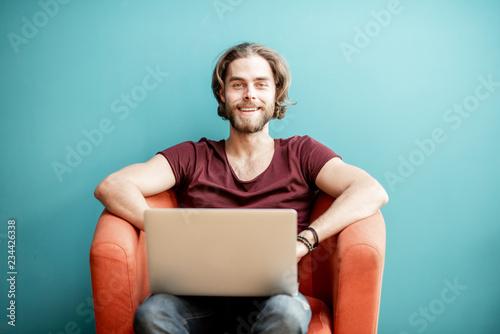 Portret młody caucasian brodaty mężczyzna z długie włosy ubierającym w koszulce pracuje z laptopem na krześle na kolorowym tle