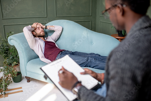 Leinwandbild Motiv Young caucasian man visiting an african psychologist lying on the comfortable couch during psychological session in the green office