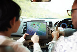 Couple in a car finding direction on a tablet with gps