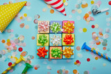 Top view of different colorful gifts with bows, party hats and confetti on blue background - 234438360