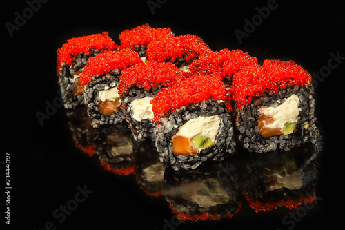 Black sushi roll with salmon, avocado, cream cheese and red caviar on stone. Japanese food