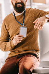 cropped view of bearded adult businessman sitting on office desk and holding blank security tag at workplace