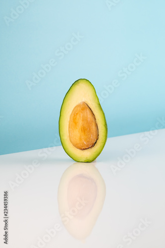 Half avocado fruit on white table. Minimalistic image of piece of alligator pear in bright studio background - 234459386
