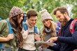 Leinwanddruck Bild - travel, tourism, hiking and people concept - group of happy friends or travelers with backpacks and map