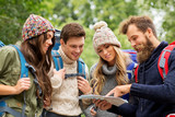 travel, tourism, hiking and people concept - group of happy friends or travelers with backpacks and map