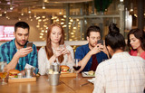 leisure, technology, lifestyle and people concept - friends with smartphones dining at restaurant - 234468148