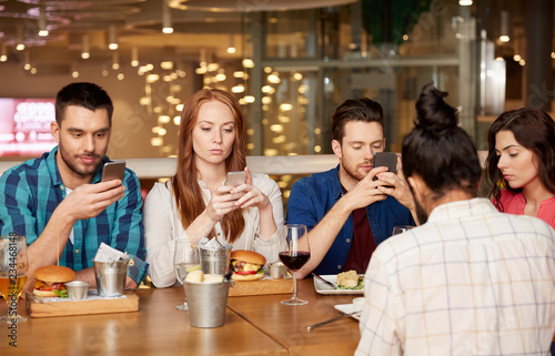 leisure, technology, lifestyle and people concept - friends with smartphones dining at restaurant