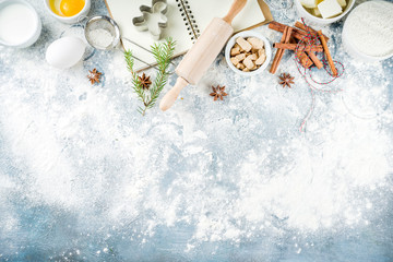 Christmas and winter baking background. Kitchen utensils and ingredients for cooking baking - flour, sugar, eggs, butter, milk, cinnamon sticks, whisk, rolling pin, anise, Blue concrete background