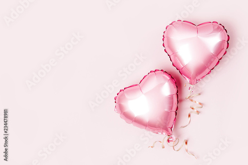 Leinwandbild Motiv Air Balloons of heart shaped foil  on pastel pink background. Love concept. Holiday celebration. Valentine's Day or wedding/bachelorette party decoration. Metallic balloon