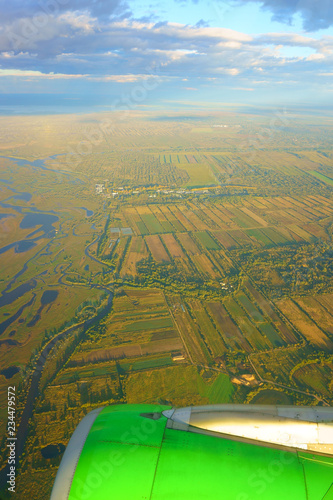 view from airplane porthole. lights of sun. Brown Field and Blue Sky - 234479572