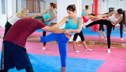 Female is training self-defence moves in pair with trainer in sporty gym.