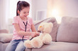 Cute girl. Dark-haired cute girl wearing jeans and pink shirt feeling entertained while playing with teddy bear