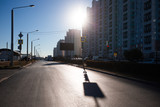 Sunny morning in the city, residential buildings and empty street © Maksim Kostenko