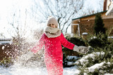 Seven-year cute girl in winter clothes playing with snow in the backyard of a house on a winter sunny day. - 234513924