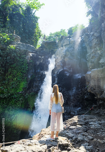 Girl on the background of a waterfall - 234519703
