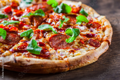 sliced Pepperoni Pizza with Mozzarella cheese, salami, chorizo, tomato sauce, pepper, Spices and Fresh arugula. Italian pizza on wooden table background - 234531302
