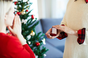 Young man opening small velvet box with engagement ring while making proposal to his girlfriend on xmas eve