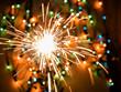 Quadro Glittering burning sparkler on colorful bokeh background.
